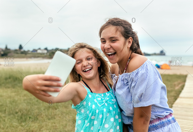 Portrait of two little sisters making a selfie with her smartphone on the beach
