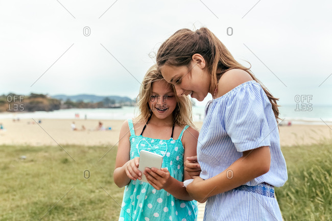 Portrait of two little sisters having fun with her smartphone on the beach
