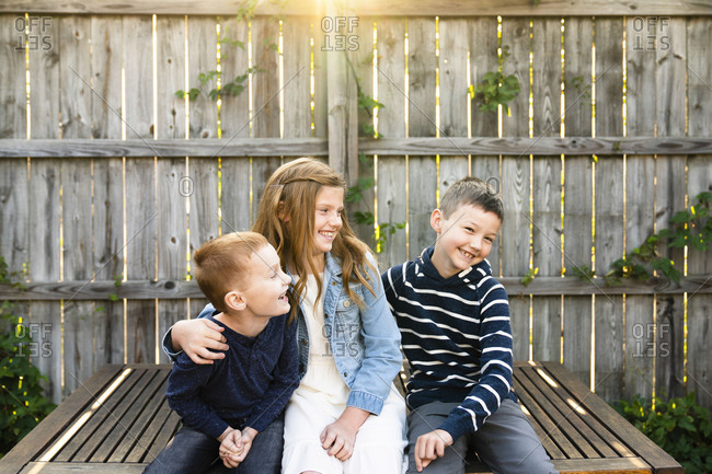 Three smiling siblings sitting together on bench