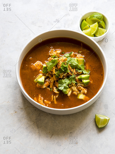 Bowl of chicken tortilla soup with lime wedges