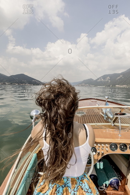 Rear view of a woman driving a motorboat