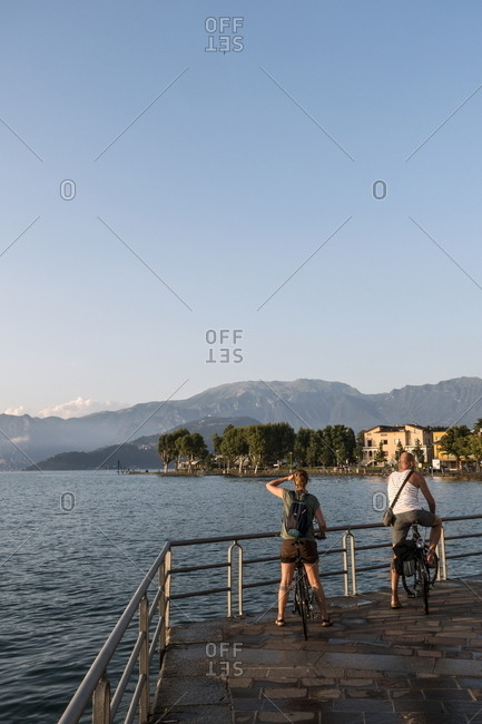 Two bikers watching sunset along the promenade at Lake Iseo, Italy