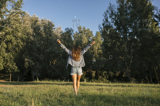 Rear view of a woman standing in a field with her hands in the air