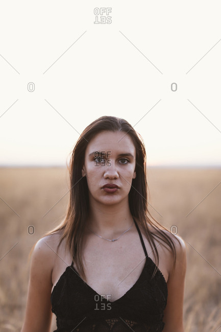 Woman with dark brown hair standing in a rural field
