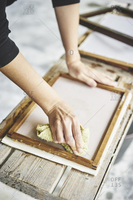 Woman attaching handmade paper to frame