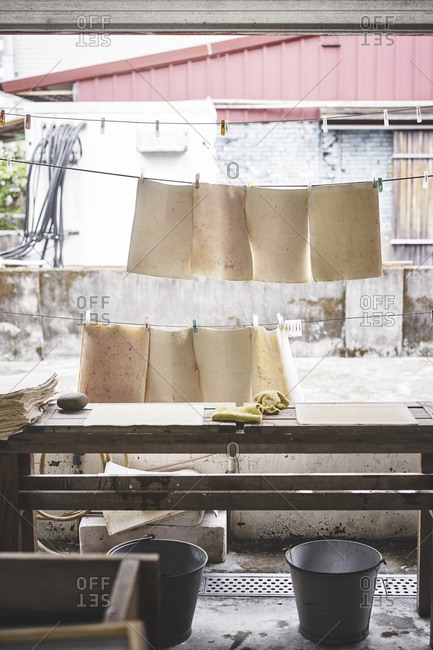 Handmade paper hanging from a line drying