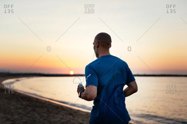 Mature man running on the beach at sunrise.