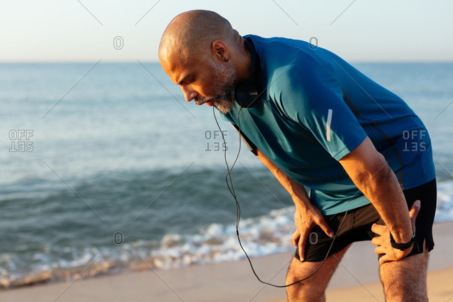 Active mature man resting on the beach after workout.