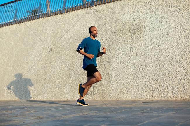 Active mature man running on the street.