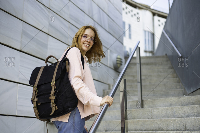 Woman walking up staircase with backpack