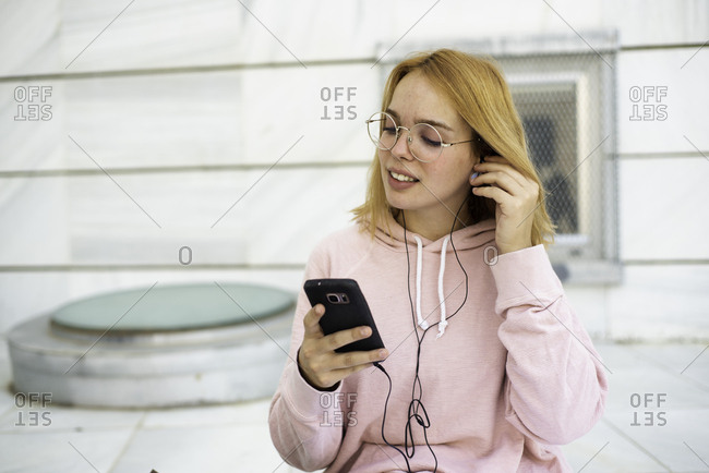 Woman watching content on smart phone with headphones