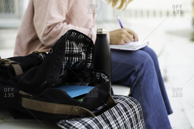 Woman sitting next to open backpack outside