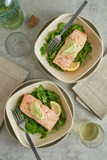 Two healthy baked salmon and arugula meals in bowls on table