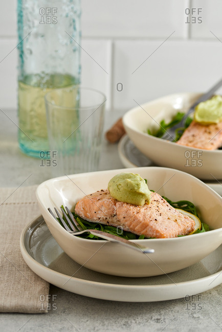 Two healthy dinners with salmon arugula and avocado dressing on kitchen counter