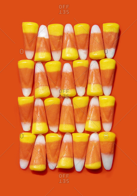 Candy corn arranged in an alternating pattern on an orange background
