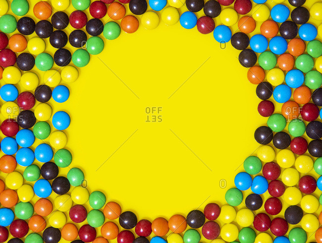 Small chocolate candies arranged in a circular pattern on a yellow background