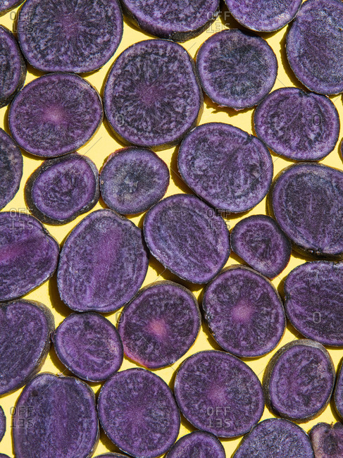 Sliced purple potatoes arranged on a yellow backdrop.
