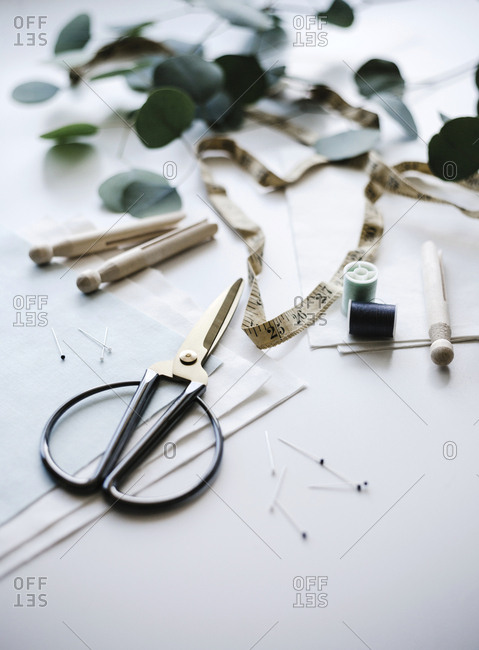 View of sewing tools with fabric thread pins scissors on a white background