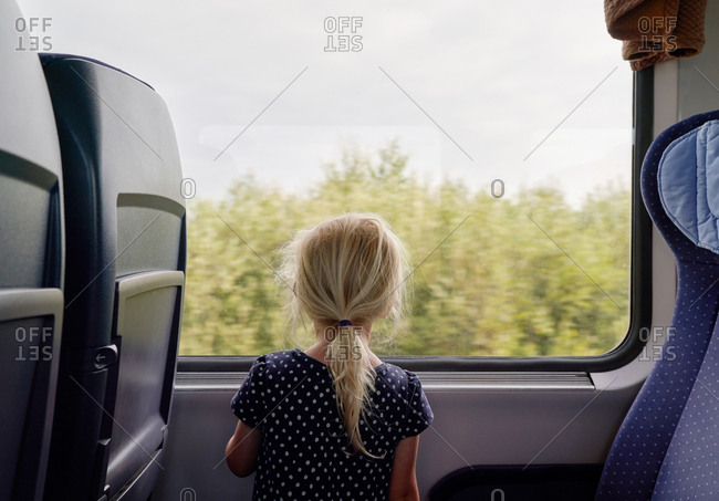 A toddler girl wearing a polka dot dress looks out a train window to a forest.