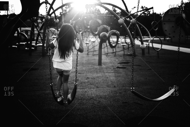 Girl standing on swing at playground