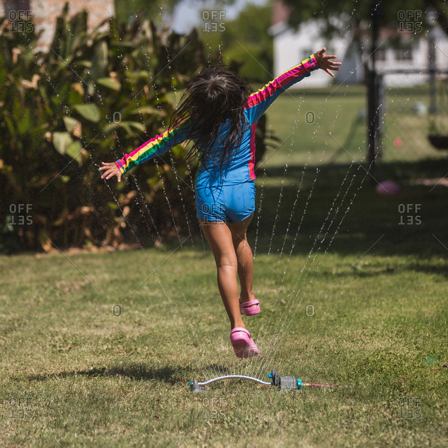 Girl with outstretched arms running through the sprinklers