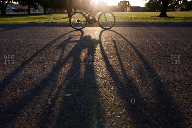 Long shadow of a child riding a bicycle on a neighborhood street