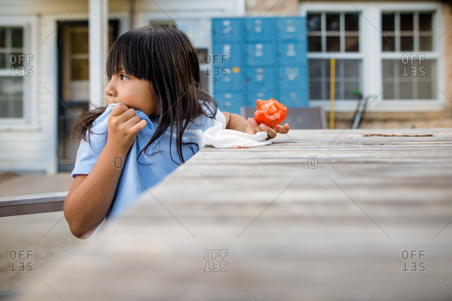 Girl wiping her mouth and looking away while eating a tomato
