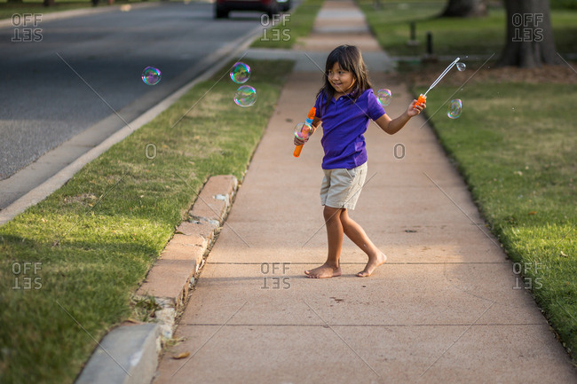 Girl playing with bubbles on the sidewalk