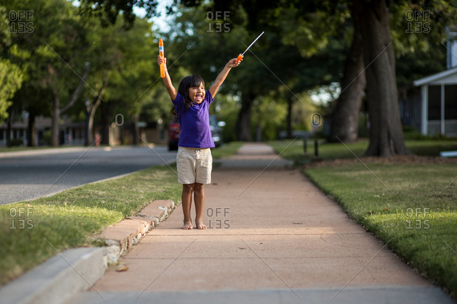 Girl standing with outstretched arms on the sidewalk