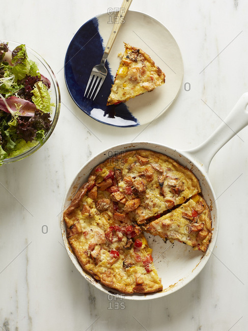Slice of quiche with peppers and chicken served with green salad