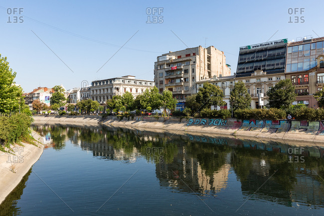 August 13, 2017: Communist era buildings reflected in the Dimbovita River in Bucharest, Romania, Europe
