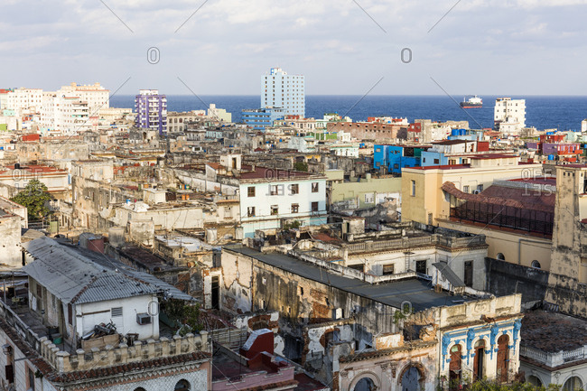 View over old building rooftops in Centro Habana, and Straits of Florida, Havana, Cuba, West Indies, Caribbean, Central America