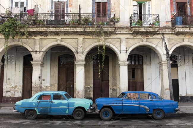 November 16, 2016: Two blue cars face nose to nose outside a dilapidated building, Havana, Cuba, West Indies, Caribbean, Central America