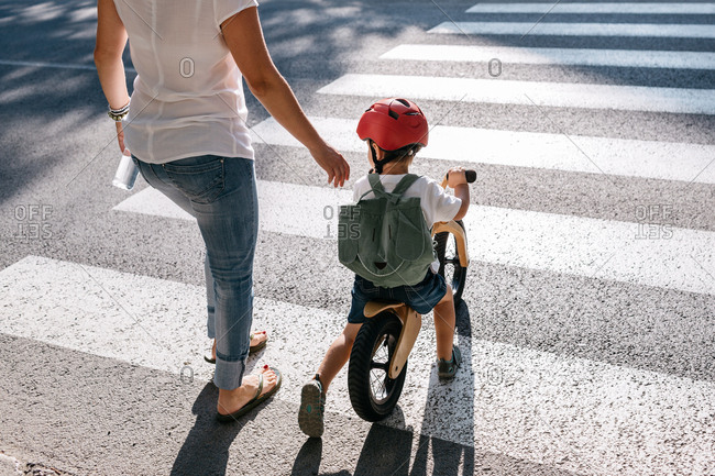 Young boy on a balance bike crossing a road with his mother.