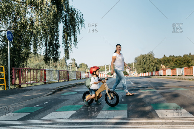 Side view of child on balance bike and his mother crossing road.