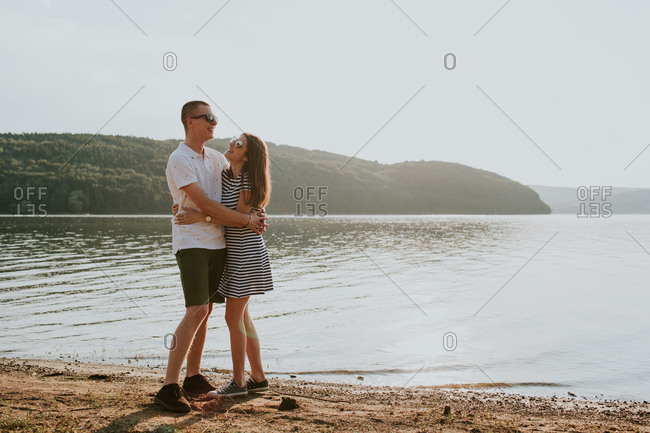 Young couple embracing while walking along the beach at sunset