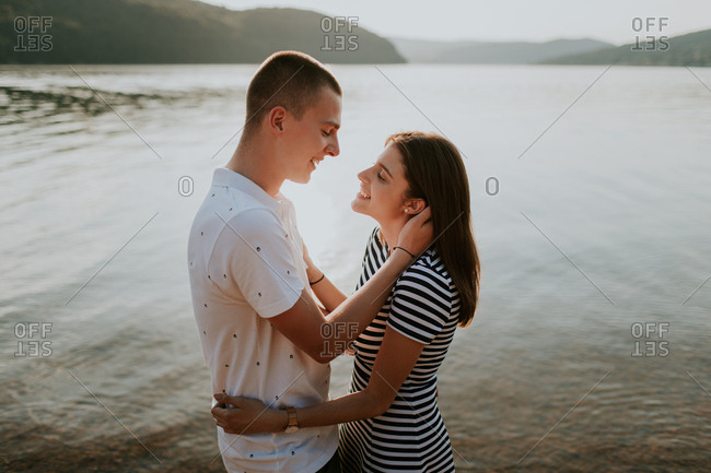 Young couple smiling at each other as they are about to kiss on the beach during a summer evening