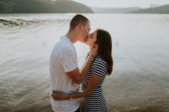 Young couple kissing on the beach at sunset on a summer evening