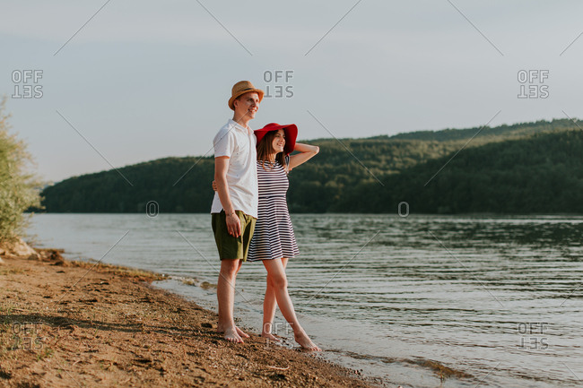 Young couple with their arms around each other while looking out at the sunset over the lake