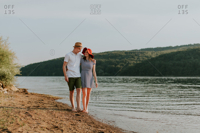 Young couple walking along the beach during a summer evening