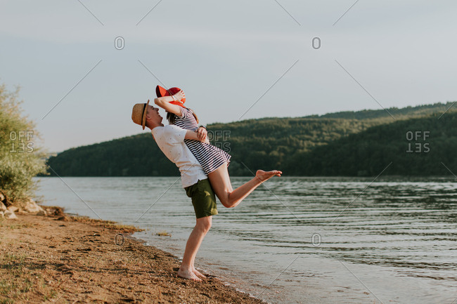 Young couple having fun on the beach at sunset on a summer evening