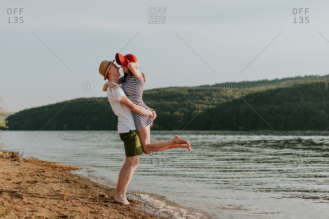 Young man lifting his girlfriend in the air on the beach during a summer evening