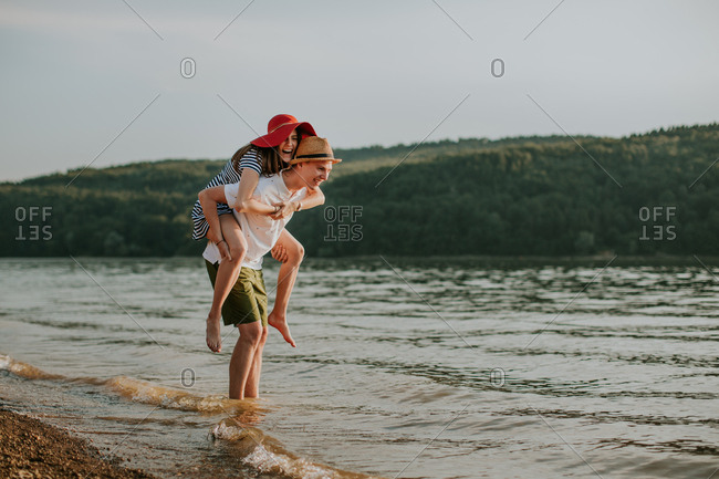 Young man carrying his girlfriend on his back while having fun on the beach at sunset