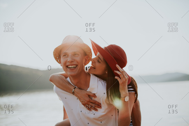 Cheerful young man carrying his girlfriend on his back while walking along the beach at sunset