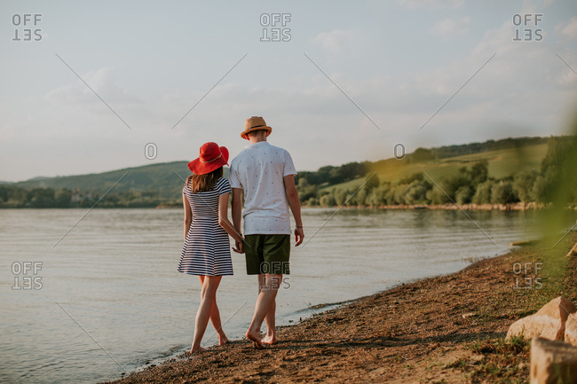 Couple holding hands while walking along the beach at sunset on a summer evening