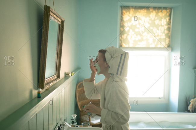 Woman applying facial mask in bathroom at home