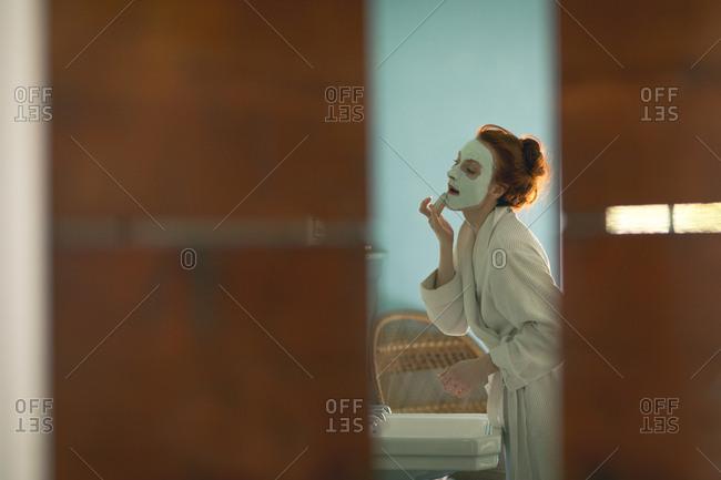 Woman applying facial mask at home