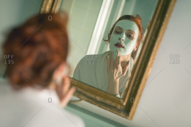 Woman applying facial mask in front of mirror in bathroom