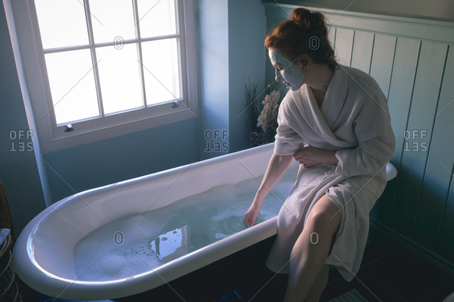 Woman sitting on bathtub checking water in bathroom at home