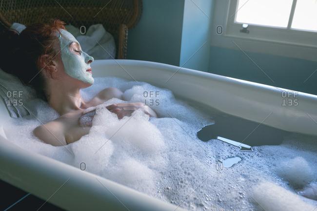 Beautiful woman relaxing in bathtub at bathroom